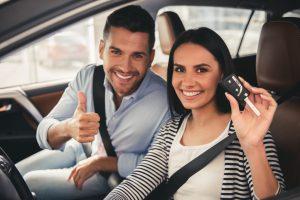 Gelukkige paar zit in nieuwe auto die de sleutel vasthoudt